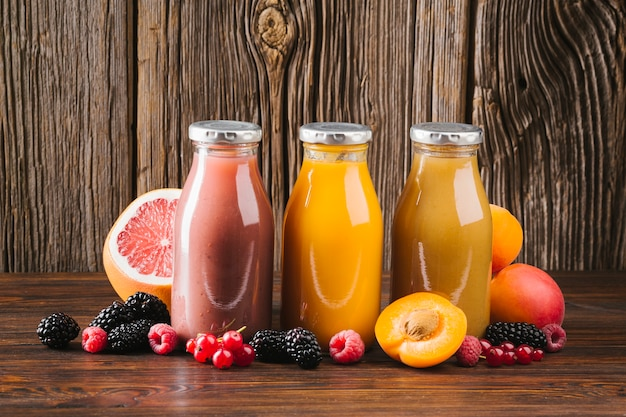 Fresh fruit smoothies on wooden background