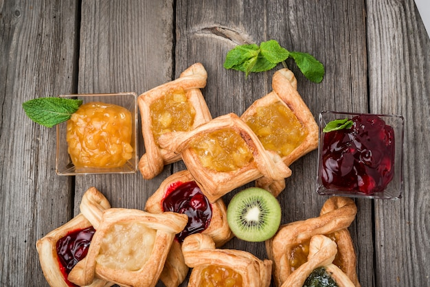 Fresh fruit tart with berries jam and mint on wooden surface