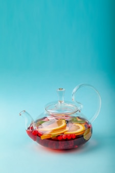 Fresh fruit tea in transparent teapot with berry