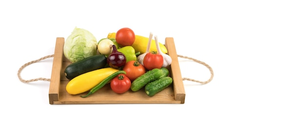 Fresh fruit:tomatoes, cucumbers, zucchini, peppers and cabbage on a wooden tray.
