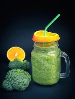 Fresh fruit vegetable broccoli celery orange smoothie bottle shake dark black