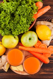 Fresh fruit and vegetables with juice on table
