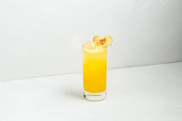Fresh fruit yellow alcohol cocktail in a highball