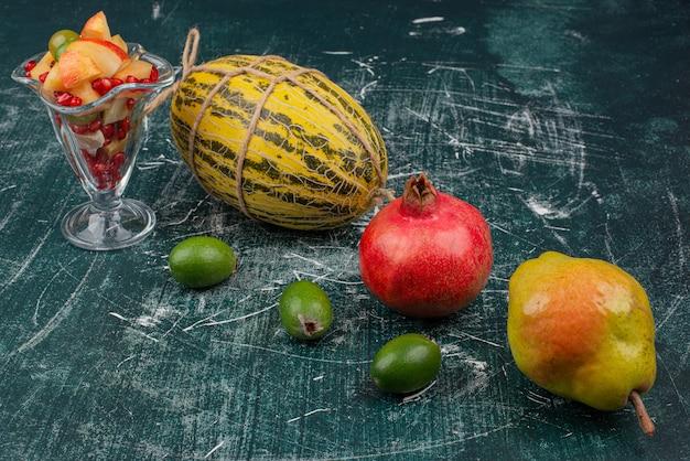 Свежие фрукты и стакан нарезанного фруктового салата на мраморной поверхности.