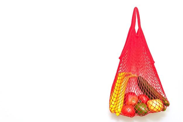 신선한 과일과 야채 사과 바나나 아보카도 토마토 오이 양파 빨간색 문자열 메쉬 가방에 흰색 절연. 확대. 플랫 레이. 선택적 소프트 포커스. 텍스트 복사 공간.