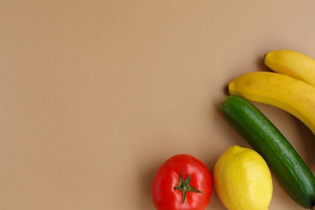 신선한 과일과 야채. 건강한 영양과 식단. 밝은 단색 배경에 레몬과 바나나, 토마토, 오이