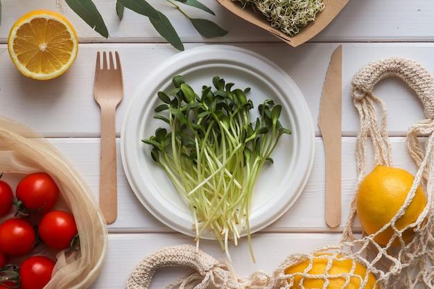 エコ使い捨て有機器具の新鮮な果物と野菜。新鮮なマイクログリーン、トマト、レモン