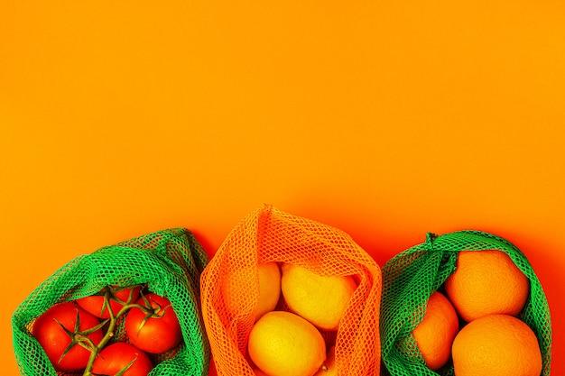 再利用可能なテキスタイルメッシュバッグに入った新鮮な果物と野菜