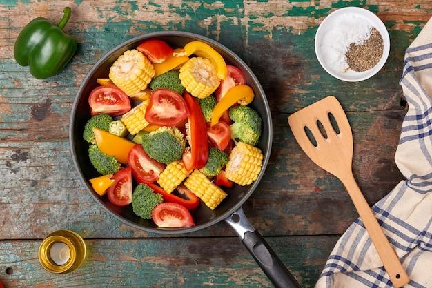 Свежие фрукты и овощи на сковороде на старом деревянном фоне