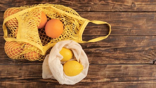 Свежие фрукты и овощи апельсины, лимоны в экологических многоразовых хлопковых мешках, биоразлагаемые на деревянном столе, стена с копией пространства плоская планировка. концепция социальной экологической ответственности