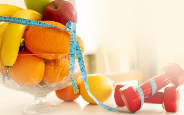 흰색 배경에 아령과 측정 테이프가 있는 신선한 과일과 야채, 건강 식품, 오렌지, 바나나, 사과, 채소. 모형 복사 공간