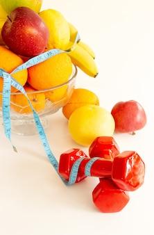 Свежие фрукты и овощи с гантелями и измерительной лентой на белом фоне, здоровое питание, апельсин, бананы, яблоко.