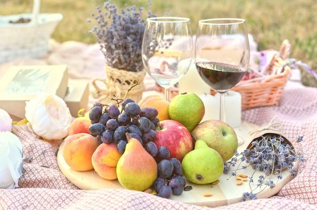Пикник на открытом воздухе со свежими фруктами и бокалом вина
