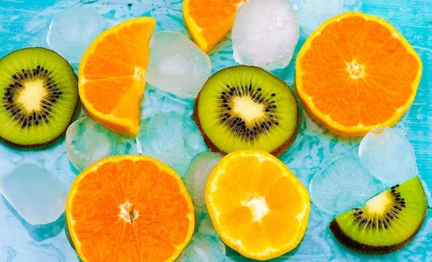 신선한 과일 배경입니다. 얼음에 신선한 과일 평면도의 조각. 오렌지와 키위 조각, 신선한 여름 배경 배너