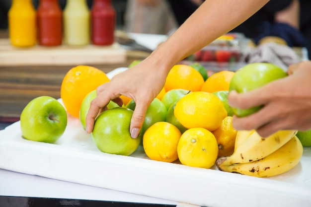 Fresh fruits (bananas, oranges, limes, apples) in market stall, as ingredients for fruit smoothies