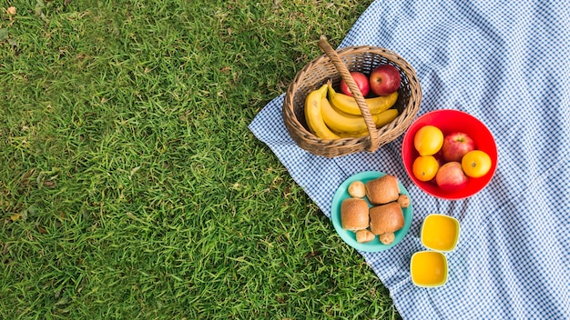 Fresh fruits; breads and glasses of juice on blanket over green grass