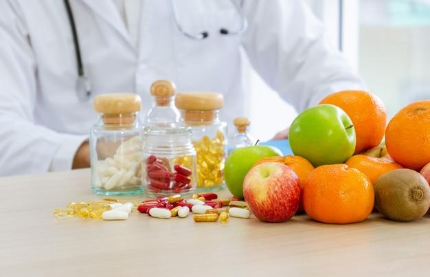 机の上の新鮮な果物、カプセル、ビタミン。首の周りに聴診器を持ち、患者の食生活を改善するための食事計画を立てている栄養専門家