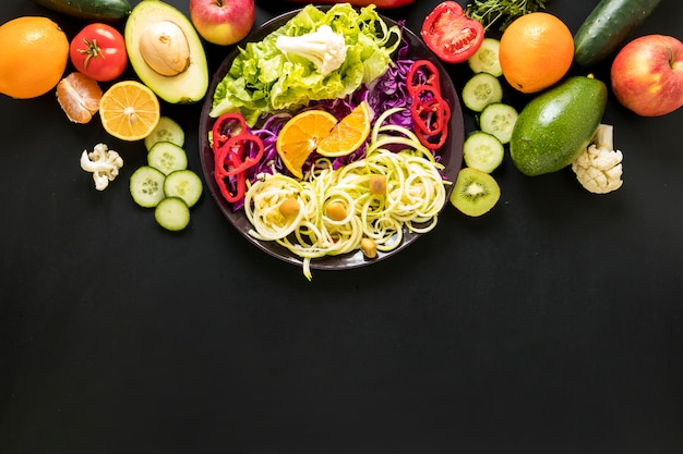 Fresh fruits and chopped vegetables against black backdrop