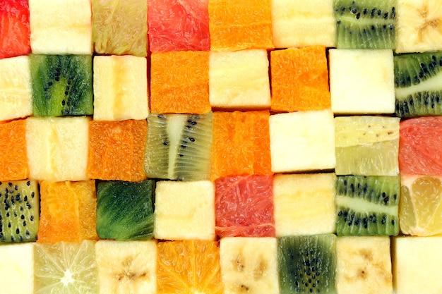 白い背景の上に一緒に積み重ねられた立方体にカットされた新鮮な果物。有用なビタミン食品