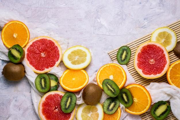 新鮮な果物、グレープフルーツ、レモン、オレンジ、キウイ、明るい石の背景。