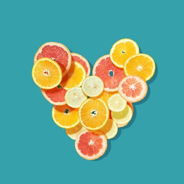 Fresh fruits heart on blue .