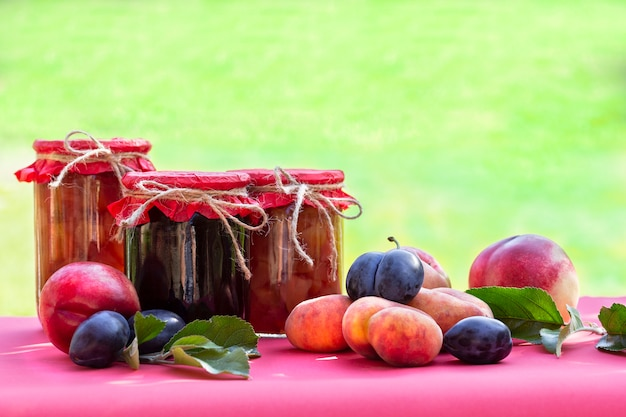 Fresh fruits and homemade jars of jam on blurred natural garden
