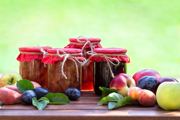 Fresh fruits and homemade jars of jam on wooden table in blurred natural garden. preserves of peaches, nectarines, plums, apple