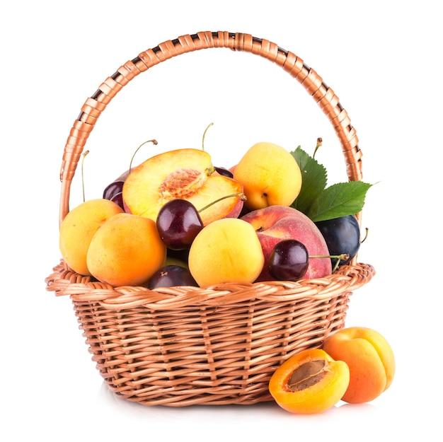 白い背景で隔離のバスケットの新鮮な果物