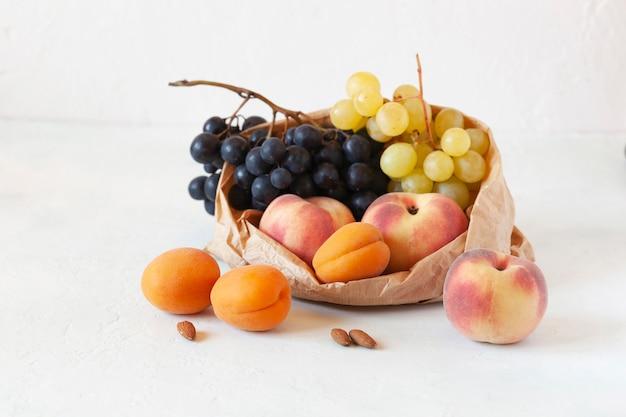 Свежие фрукты в бумажном пакете, концепция нулевых отходов, здоровое питание, вегетарианская еда, белый фон, вид сбоку