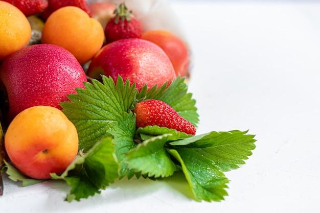 キッチンのテーブルのエココットンバッグに新鮮な果物。リンゴとナシ、アプリコットとイチゴ、廃棄物ゼロの取引コンセプト。プラスチック禁止。