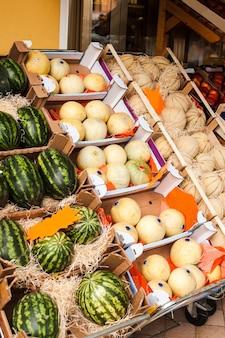 Свежие фрукты дыни черный и белый виноград на рынке