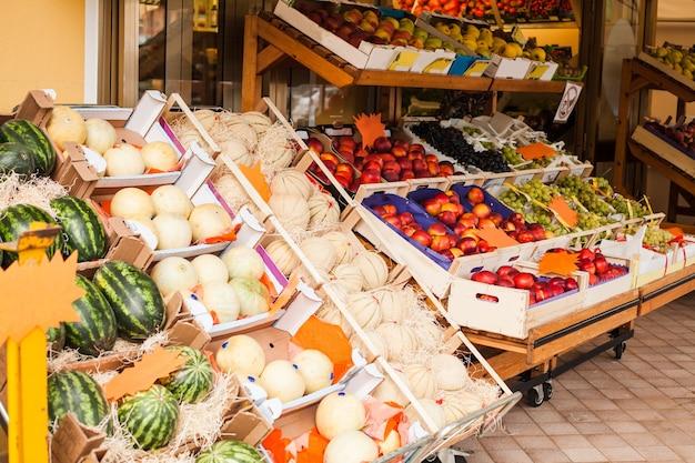 Свежие фрукты нектарины и белые дыни на рынке