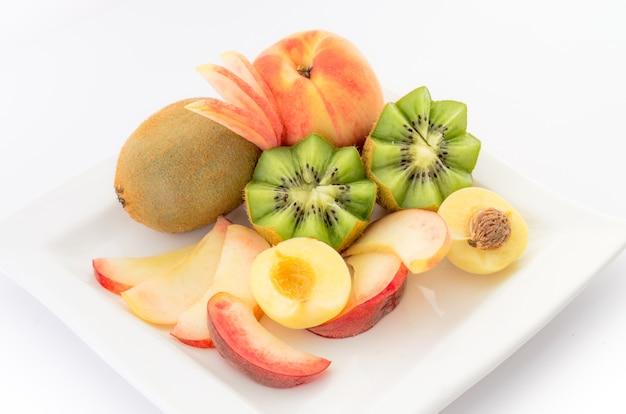 Свежие фрукты на белой тарелке крупным планом