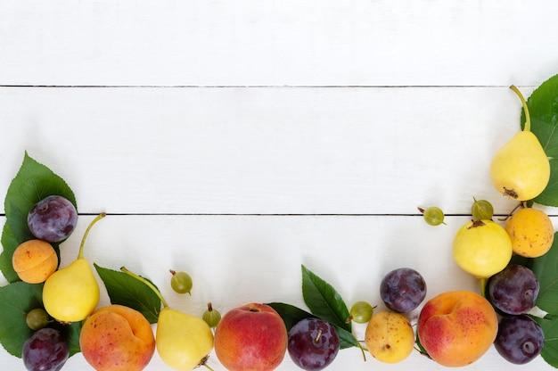白い木製のテーブルの上の新鮮な果物。スペースをコピーします。