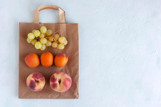 紙袋の新鮮な果物、ゼロウェイストと健康食品のコンセプト、白い背景、コピースペース、上面図