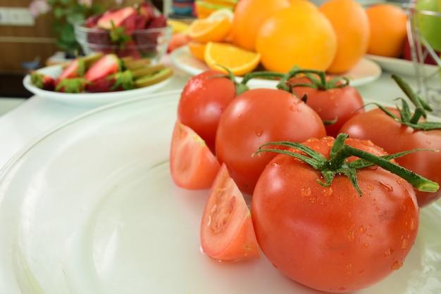 Свежие фрукты на белом фоне. свежие красные помидоры с каплями воды
