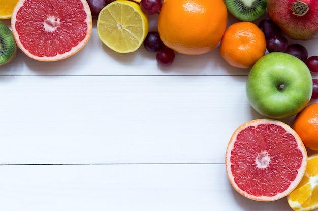 Свежие фрукты на фоне рамки белые деревянные доски