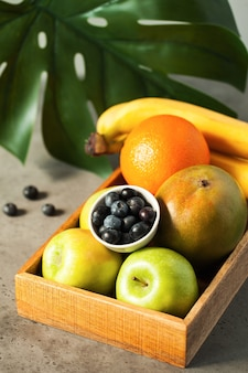 Fresh fruits oranges, apples, bananas, mangoes and blueberries in a wooden box with palm leaf