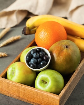 Fresh fruits oranges, apples, bananas, mangoes and blueberries in a wooden box.