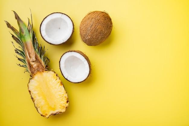 노란색 질감의 여름 배경에 신선한 과일, 파인애플, 코코넛 세트, 텍스트 복사 공간이 있는 평면도