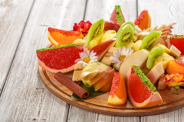 Fresh fruits in plate on wooden table