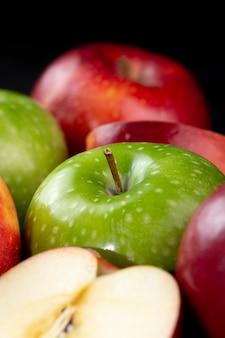 어두운 책상에 고립 된 신선한 과일 빨강 및 녹색 육즙 부드러운 사과
