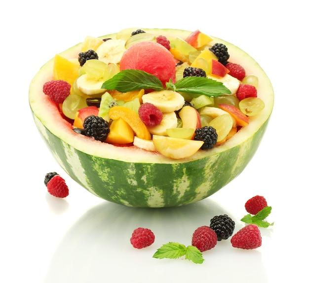 Салат из свежих фруктов в арбузе и ягодах, на белом