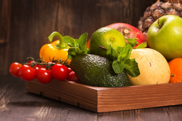 Fresh fruits and vegetables in a wooden tray