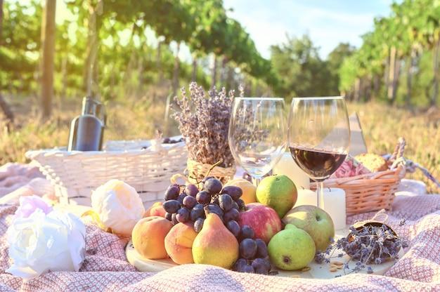 Frutta fresca e picnic in vetro di vino all'aperto