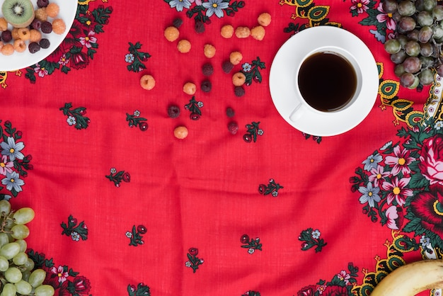 Fresh fruits with black coffee cup on red floral tablecloth