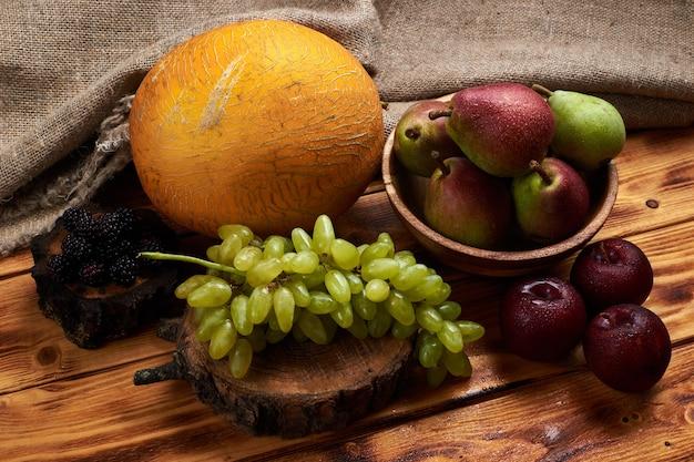木製のテーブルにメロン、ブドウ、プラム、梨、ブラックベリーと新鮮な果物