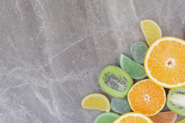 Fresh fruits with sweet marmalades on marble background.