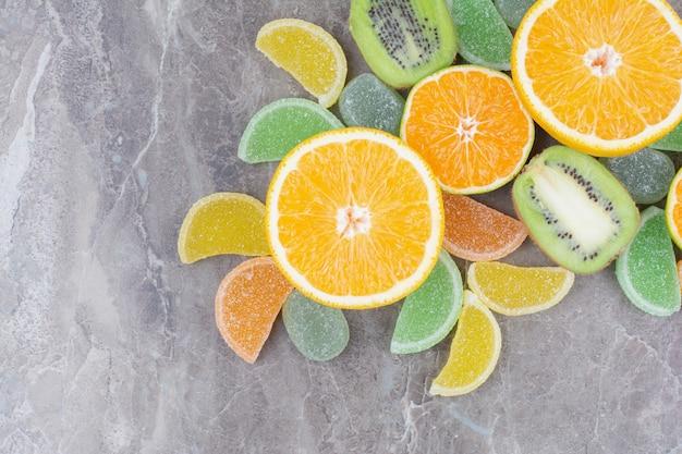 Свежие фрукты со сладким мармеладом на мраморном фоне.