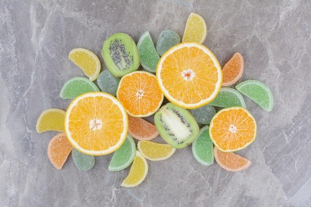 大理石の背景に甘いマーマレードと新鮮な果物。